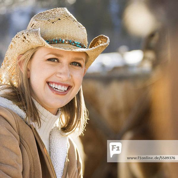 Young Caucasian Woman wearing Cowboy-Hut lächelnd auf Betrachter.