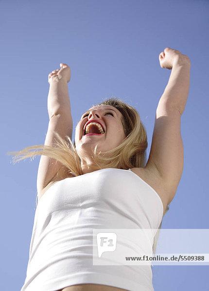 Young Woman with Arms raised an blauer Himmel  Ansicht von unten jubeln
