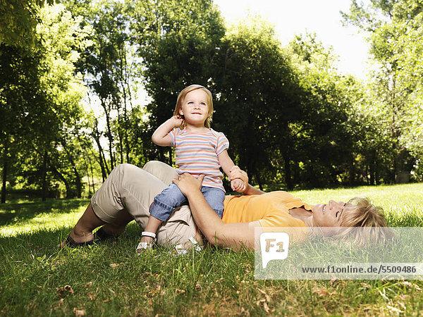 Caucasian Mitte erwachsen frau liegen im Gras im Park mit Kleinkind Tochter auf ihrem Schoß sitzt.