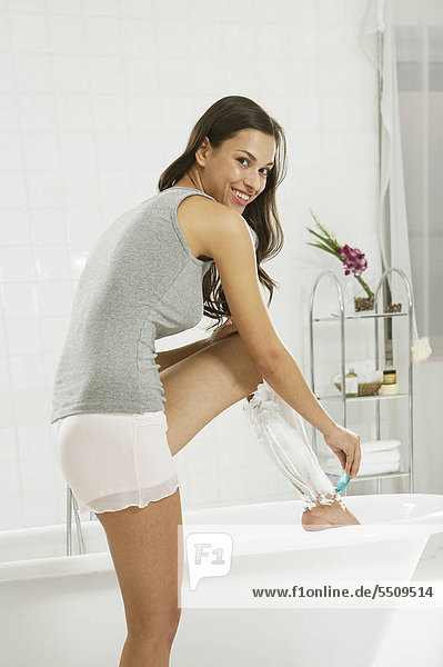 Junge Frau rasiert sich die Beine