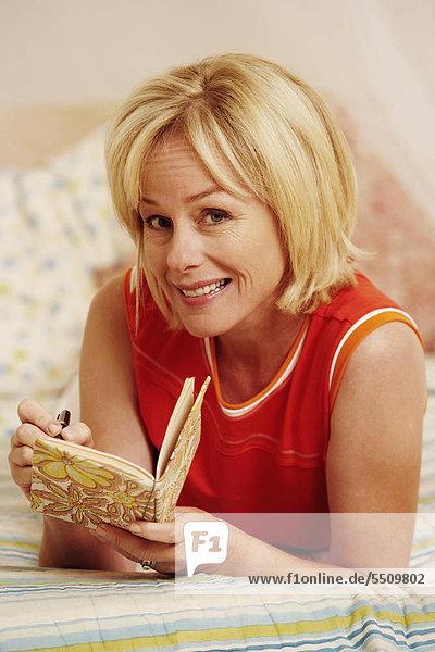 liegend liegen liegt liegendes liegender liegende daliegen Portrait Frau schreiben Bett reifer Erwachsene reife Erwachsene Tagebuch