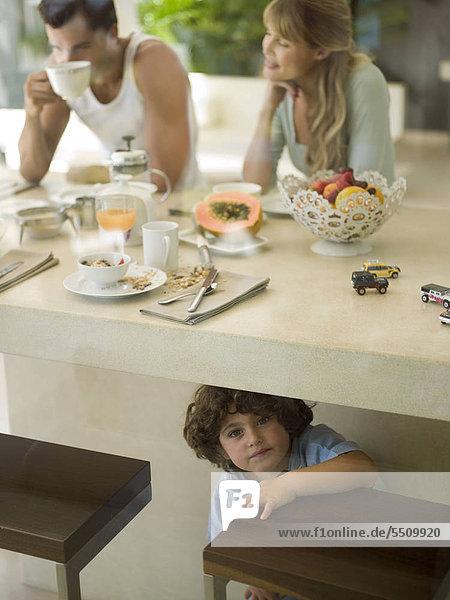 Eltern beim Frühstück  Sohn krabbelt unter dem Tisch