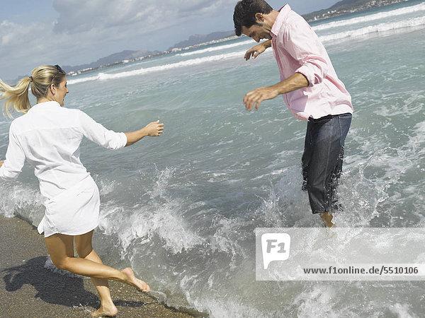 Junges Paar plantscht im flachen Wasser