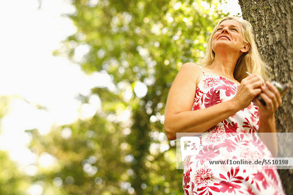 Handy niedrig Frau lächeln halten reifer Erwachsene reife Erwachsene Kurznachricht Ansicht Flachwinkelansicht Winkel