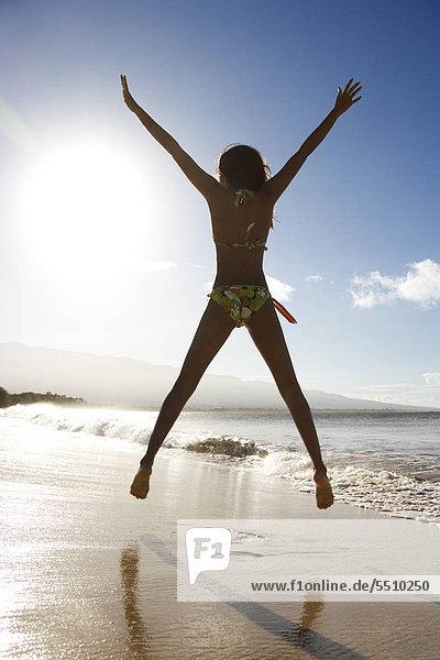 Rückansicht des Mädchen im Bikini am Strand mit Begeisterung springen