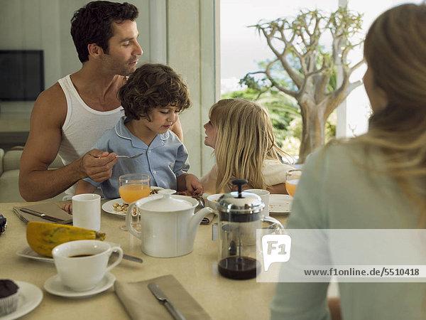 Eltern und Kinder albern beim Frühstück herum