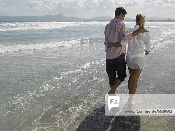 Junges Paar macht einen Strandspaziergang