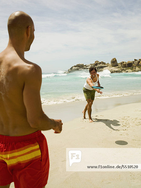 Men playing frisbee on the beach.