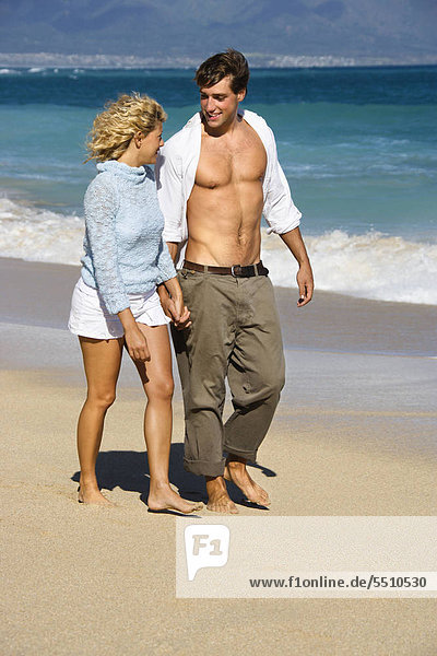 Attractive Couple holding Hands walking on Beach smiling at einander in Maui  Hawaii.