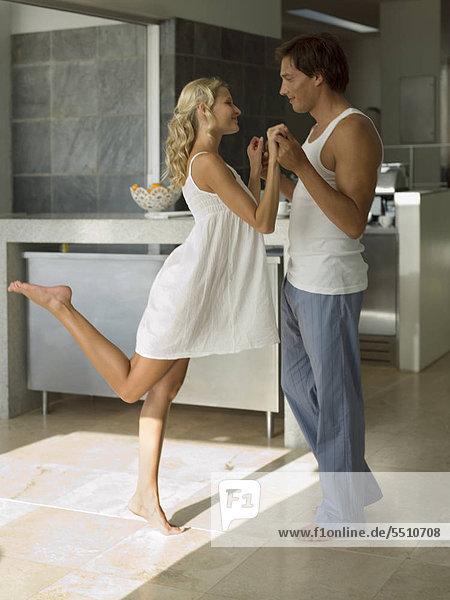 Junges Paar tanzt in der Küche