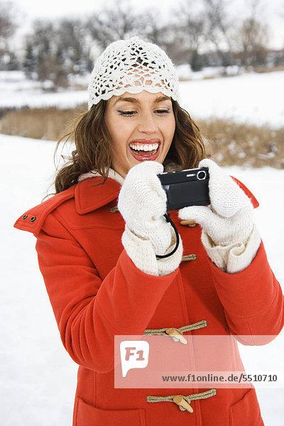 Lächelnd Caucasian junge Erwachsene Weibchen in Winterkleidung im Freien mit digitalen Kamera.