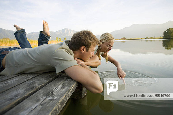 Couple lying down on a pier
