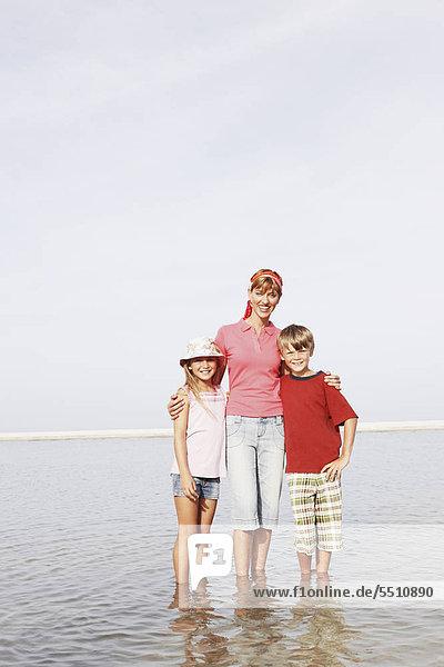 Familie posiert am Strand