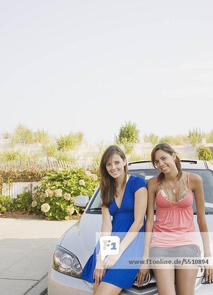 Junge Frauen sitzen auf Auto