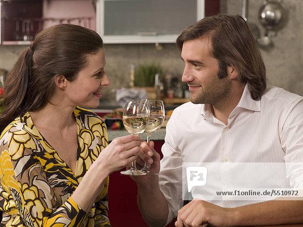 Mann   Frau stoßen mit Weißwein an