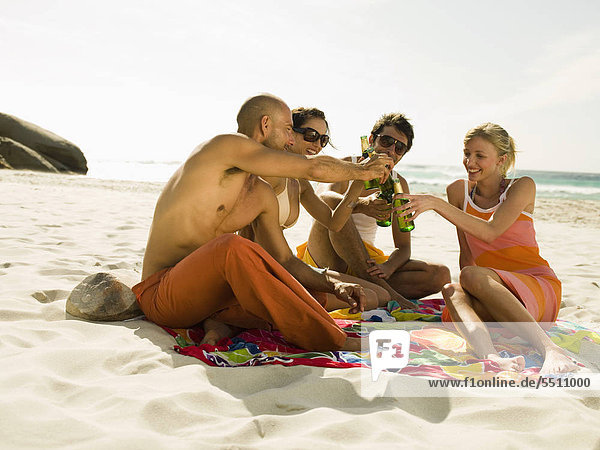 Friends drinking beer on the beach.
