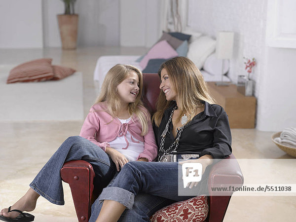 Mid adult woman sitting with her daughter on a couch and smiling