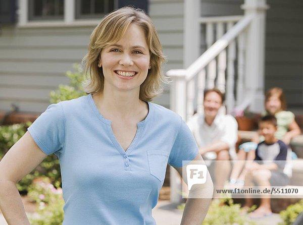 Portrait of Woman with Familie im Hintergrund