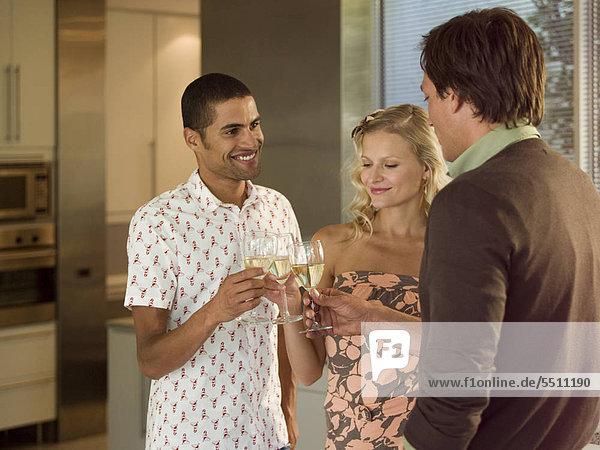Zwei Männer und eine Frau stoßen mit Sekt an