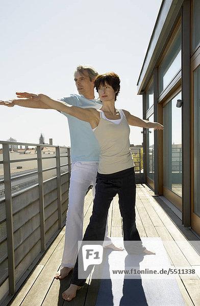 Älteres Paar beim Yoga auf der Dachterrasse