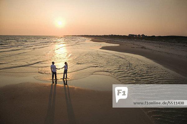 Luftbild des romantischen Couple Standing Strand Betrieb Hände auf Bald Head Island  North Carolina.