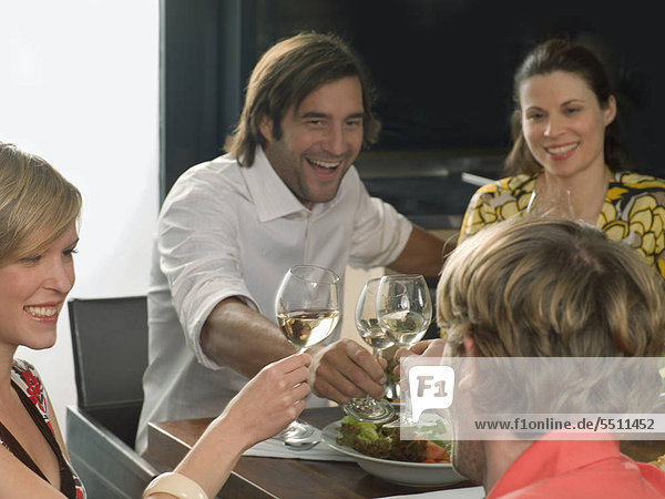 Zwei Pärchen stoßen mit Wein an
