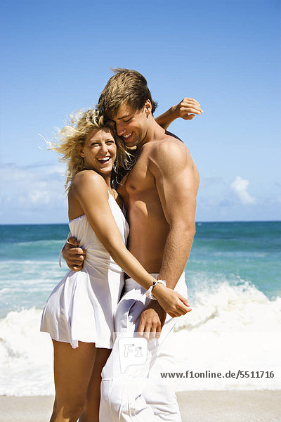Couple embracing and smiling am Strand von Maui  Hawaii.
