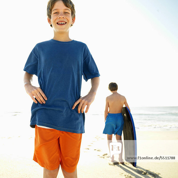 Caucasian boy with hands on hips with another Caucasian boy with bodyboard in background.