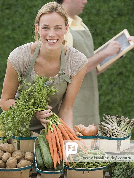 Frau neben Körbe mit Gemüse