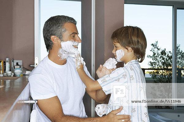 Vater und Sohn seifen sich gegenseitig mit Rasierschaum ein