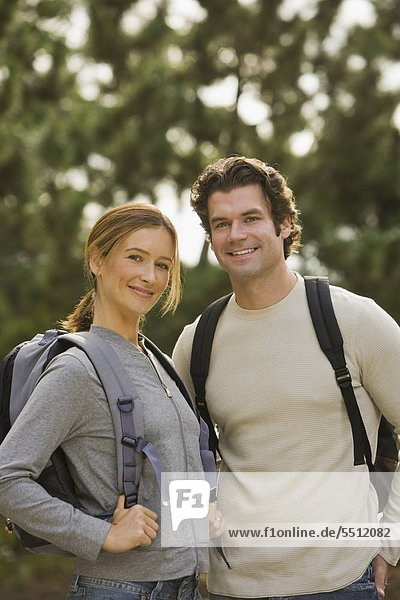 Couple wearing backpacks in woods