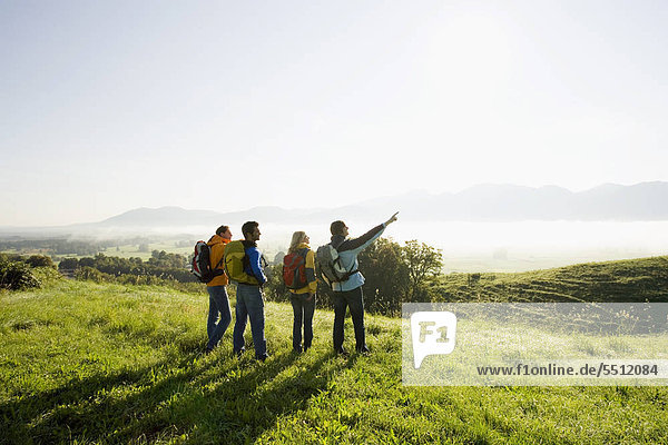 Four friends with their backpacks on a hiking trip.