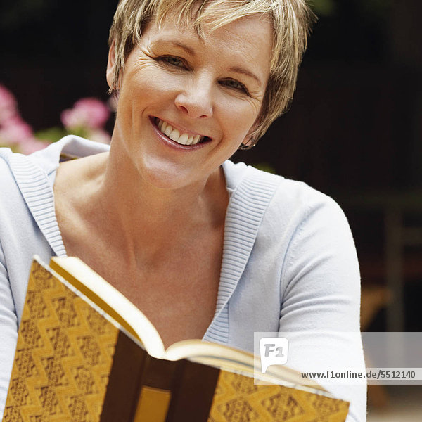 Portrait of a mature woman holding a book and smiling