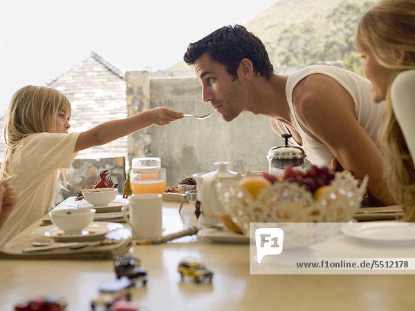 Eltern mit Tochter am Frühstückstisch