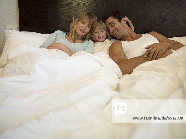 Eltern und Tochter faulenzen im Bett