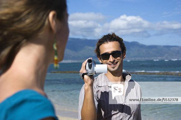 Mid-adult kaukasischen Mann am Strand zeigenden-Videokamera bei Frau.