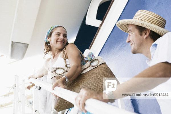 Mitte adult Couple Standing auf der Treppe eines Kreuzfahrtschiffes und Blick auf einander