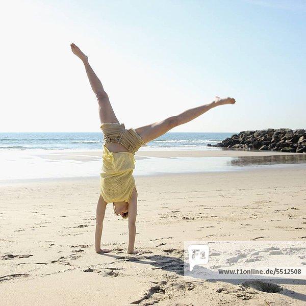 Frau macht Cartwheel am Strand