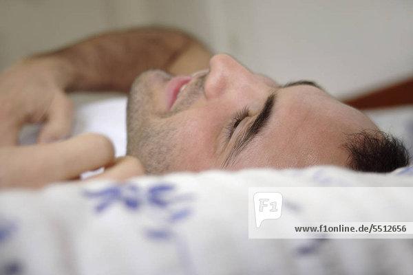 Junger Mann im Bett liegend lächelnd und entspannen
