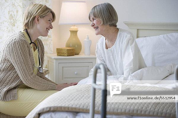 Krankenschwester im Gespräch mit senior Woman in bed