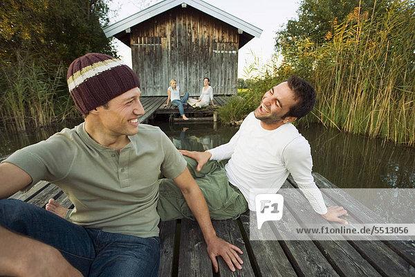 Vier Freunde sitzen vor einer Holzhütte am See