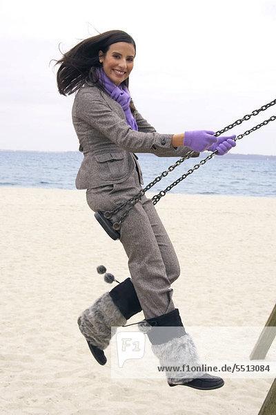 Junge Frau schaukelt übermütig am Strand