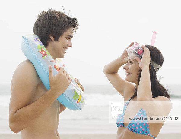 Paar lächeln einander am Strand