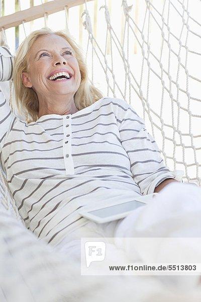 liegend,liegen,liegt,liegendes,liegender,liegende,daliegen,Senior,Senioren,Frau,Fröhlichkeit,Hängematte,Tablet PC