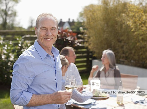 Portrait of smiling man drinking wine in garden with friends pe0080399