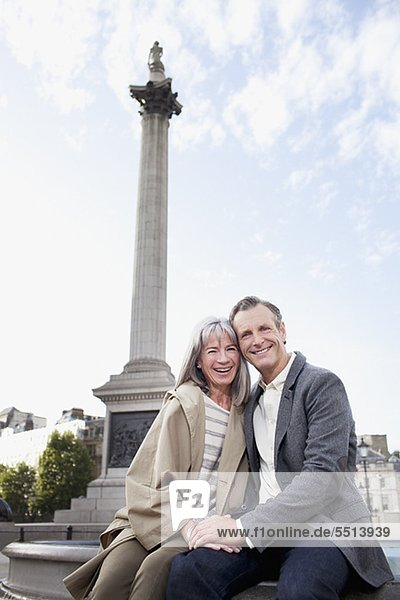 Portrait of smiling couple under London monument pe0080567