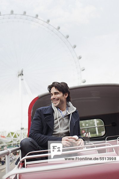 Happy man riding double decker bus in London pe0080626