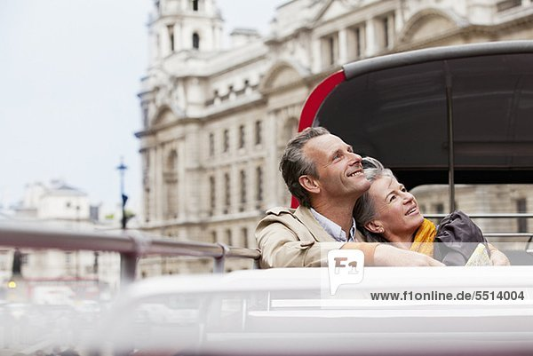 Lächelndes Paar im Doppeldeckerbus in London schaut nach oben
