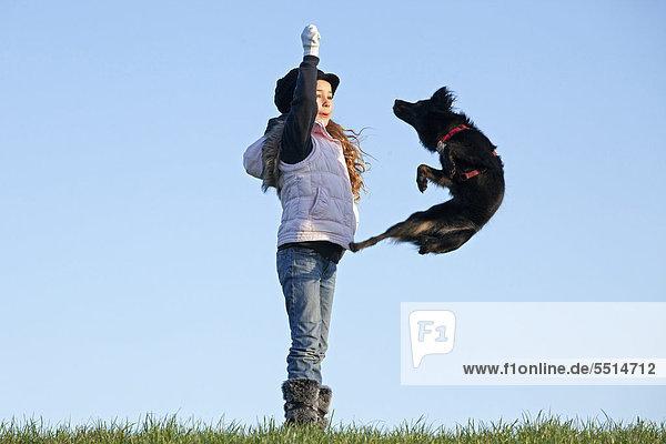 Girl making a dog jump