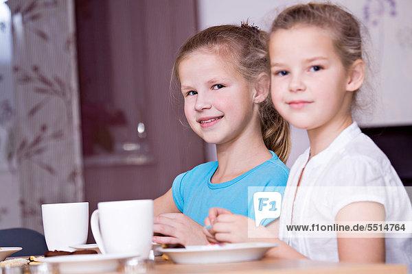 Zwei Mädchen  11 und 8 Jahre  sitzen am gedeckten Tisch